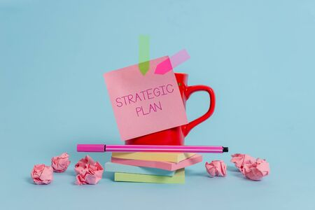 Writing note showing Strategic Plan. Business concept for A process of defining strategy and making decisions Coffee cup pen note banners stacked pads paper balls pastel background