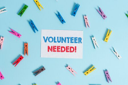 Handwriting text writing Volunteer Needed. Conceptual photo need work for organization without being paid Colored clothespin rectangle shaped reminder paper light blue background Banco de Imagens