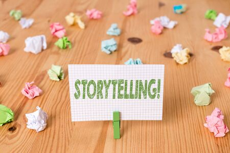 Conceptual hand writing showing Storytelling. Concept meaning activity writing stories for publishing them to public Colored crumpled papers wooden floor background clothespin