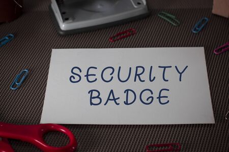 Word writing text Security Badge. Business photo showcasing Credential used to gain accessed on the controlled area Scissors and writing equipments plus plain sheet above textured backdrop