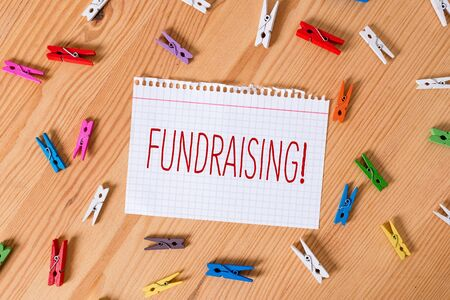 Word writing text Fundraising. Business photo showcasing seeking to generate financial support for charity or cause Colored clothespin papers empty reminder wooden floor background office 版權商用圖片