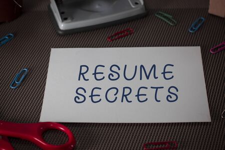Word writing text Resume Secrets. Business photo showcasing Tips on making amazing curriculum vitae Standout Biography Scissors and writing equipments plus plain sheet above textured backdrop