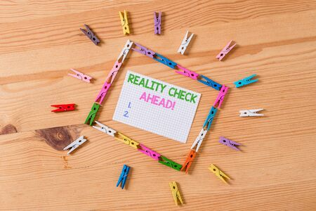 Writing note showing Reality Check Ahead. Business concept for makes them recognize truth about situations or difficulties Colored clothespin papers empty reminder wooden floor background office Stock Photo