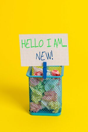 Text sign showing Hello I Am New. Business photo showcasing used as greeting or to begin telephone conversation Trash bin crumpled paper clothespin empty reminder office supplies yellow
