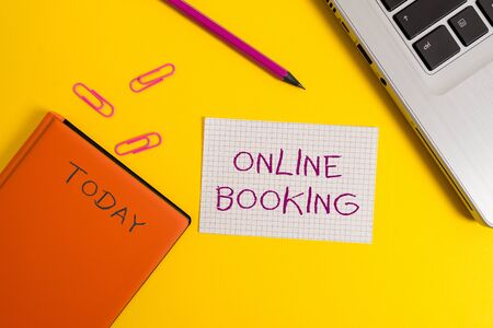 Handwriting text writing Online Booking. Conceptual photo Reservation through internet Hotel accommodation Plane ticket Laptop clips pencil paper sheet hard cover notebook colored background