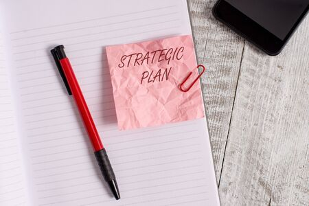 Conceptual hand writing showing Strategic Plan. Concept meaning A process of defining strategy and making decisions Wrinkle paper notebook and stationary placed on wooden background Stockfoto