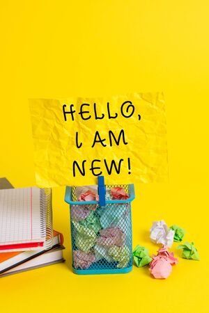 Conceptual hand writing showing Hello I Am New. Concept meaning used as greeting or to begin telephone conversation Trash bin crumpled paper clothespin office supplies yellow