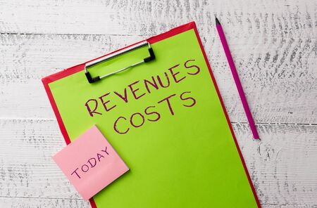 Word writing text Revenues Costs. Business photo showcasing Total amount of money in Manufacturing and Delivery a product Metal clipboard paper sheets marker sticky notes pad wooden background