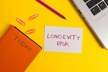 Handwriting text writing Longevity Risk. Conceptual photo Potential threat due to increasing lifespan of pensioners Laptop clips pencil paper sheet hard cover notebook colored background Banco de Imagens
