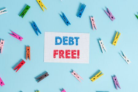 Handwriting text writing Debt Free. Conceptual photo does not owning any money or things to any individual or companies Colored clothespin rectangle shaped reminder paper light blue background