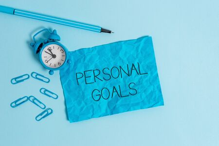 Word writing text Personal Goals. Business photo showcasing Target set by a demonstrating to influence his efforts Motivation Metal alarm clock blank crushed sheet marker clips sky colored background Stock Photo