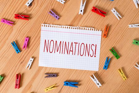 Word writing text Nominations. Business photo showcasing action of nominating or state being nominated for prize Colored clothespin papers empty reminder wooden floor background office Stock Photo