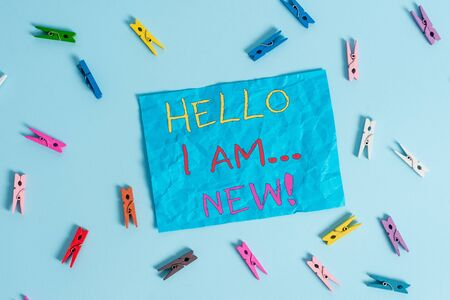 Word writing text Hello I Am New. Business photo showcasing used as greeting or to begin telephone conversation Colored clothespin rectangle shaped reminder paper light blue background