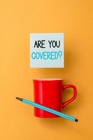 Writing note showing Are You Covered Question. Business concept for asking showing if they had insurance in work or life Front view coffee cup colored sticky note pen yolk color background 写真素材