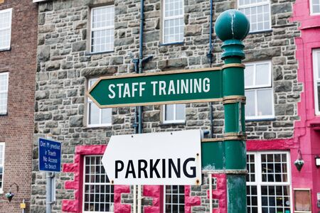 Conceptual hand writing showing Staff Training. Concept meaning A program that helps employees to learn specific knowledge Advertisement concept with empty copy space on the road sign