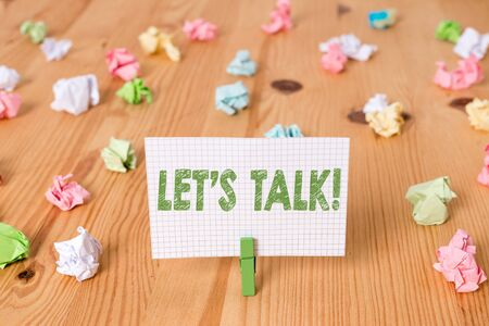 Conceptual hand writing showing Let S Talk. Concept meaning they are suggesting beginning conversation on specific topic Colored crumpled papers wooden floor background clothespin