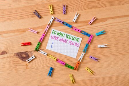 Writing note showing Do What You Love Love What You Do. Business concept for you able doing stuff you enjoy it to work in better places then Colored clothespin papers empty reminder wooden floor background office