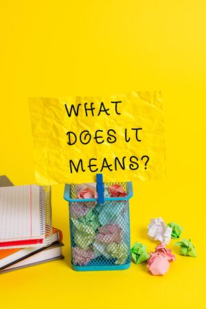 Conceptual hand writing showing What Does It Means question. Concept meaning asking someone about meaning something said and you do not understand Trash bin crumpled paper clothespin office supplies yellow Foto de archivo