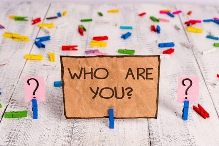 Koncepcyjne pismo ręczne pokazujące, kim jesteś pytanie. Pojęcie oznaczające pytanie wykazujące tożsamość lub demonstrujące informacje Kruszący się arkusz ze spinaczami do papieru umieszczonymi na drewnianym stole