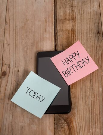 Handwriting text Happy Birthday. Conceptual photo The birth anniversary of a demonstrating is celebrated with presents Smartphone two colored sticky notes lying vintage old wooden background