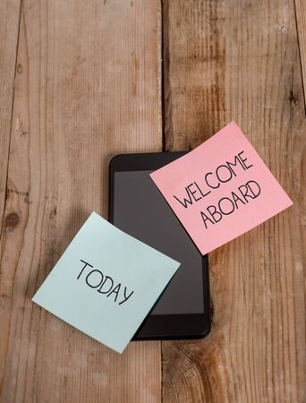 Handwriting text Welcome Aboard. Conceptual photo Expression of greetings to a demonstrating whose arrived is desired Smartphone two colored sticky notes lying vintage old wooden background