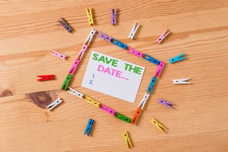Writing note showing Save The Date. Business concept for Organizing events well make day special event organizers Colored clothespin papers empty reminder wooden floor background office
