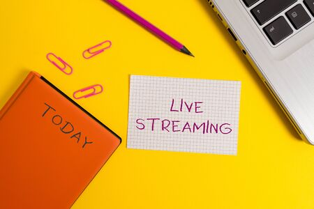Handwriting text writing Live Streaming. Conceptual photo Transmit live video coverage of an event over the Internet Laptop clips pencil paper sheet hard cover notebook colored background