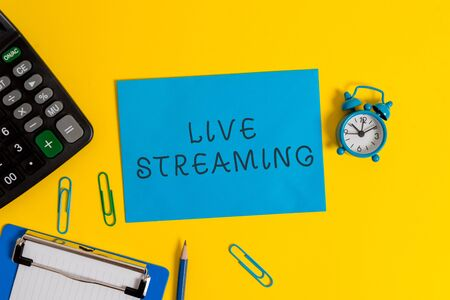 Handwriting text Live Streaming. Conceptual photo Transmit live video coverage of an event over the Internet Clipboard sheet clips note calculator pencil alarm clock colored background