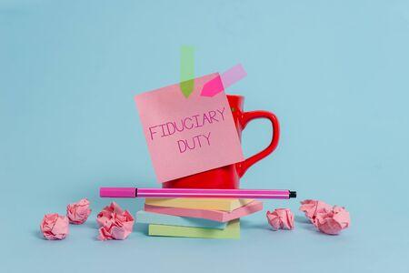 수탁자의 의무를 나타내는 메모 작성. 다른 커피 컵 펜 메모 배너 쌓인 패드 종이 공 파스텔 배경의 최선의 이익을 위해 행동해야 하는 법적 의무에 대한 비즈니스 개념 스톡 콘텐츠