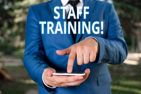 Writing note showing Staff Training. Business concept for learn specific knowledge improve perforanalysisce in current roles Businessman with pointing finger in front of him