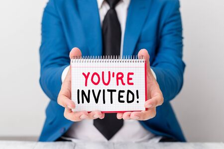 Handwriting text You Re Invited. Conceptual photo make a polite friendly request to someone go somewhere Man holds empty paper with copy space in front of him Copy Space