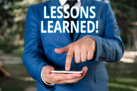 Writing note showing Lessons Learned. Business concept for experiences distilled project that should actively taken Businessman with pointing finger in front of him Imagens