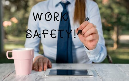 Writing note showing Work Safety. Business concept for policies and procedures in place to ensure health of employees Female business person sitting by table and holding mobile phone