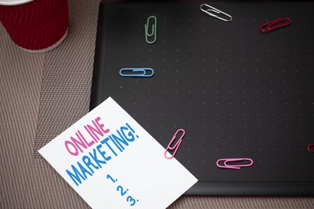 Text sign showing Online Marketing. Business photo text leveraging web based channels spread about companys brand Scissors and writing equipments plus math book above textured backdrop