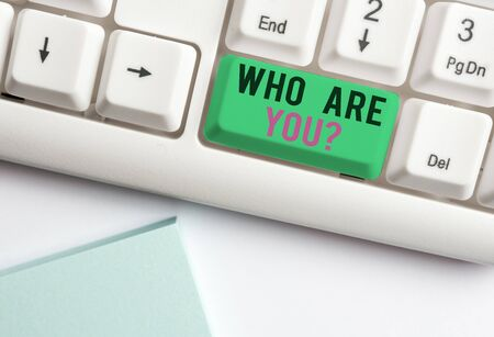 Conceptual hand writing showing Who Are You question. Concept meaning asking about demonstrating identity or demonstratingal information White pc keyboard with note paper above the white background