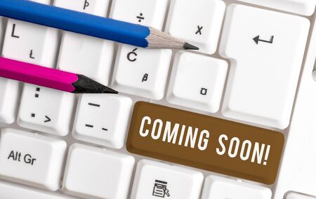 Conceptual hand writing showing Coming Soon. Concept meaning event or action that will happen after really short time White pc keyboard with note paper above the white background