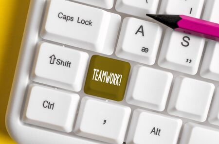 Writing note showing Teamwork. Business concept for combined action of group especially when effective and efficient White pc keyboard with note paper above the white background