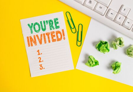 Conceptual hand writing showing You Re Invited. Concept meaning make a polite friendly request to someone go somewhere Flat lay with copy space white paper with paper clips on the table