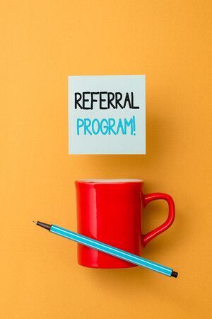Writing note showing Referral Program. Business concept for internal recruitment method employed by organizations Front view coffee cup colored sticky note pen yolk color background