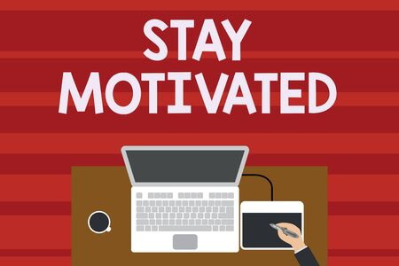 Text sign showing Stay Motivated. Business photo text Reward yourself every time you reach a goal with knowledge Upper view laptop wooden desk worker drawing tablet coffee cup office