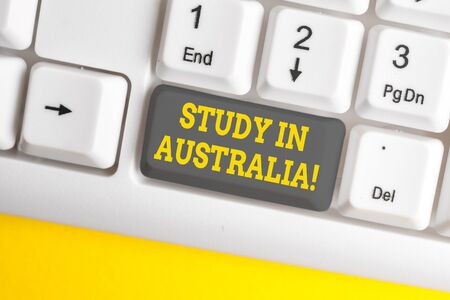 Handwriting text writing Study In Australia. Conceptual photo going into foreign country order complete your studies White pc keyboard with empty note paper above white background key copy space 写真素材