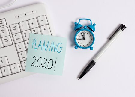 Text sign showing Planning 2020. Business photo text process of making plans for something next year White pc keyboard with empty note paper above white background