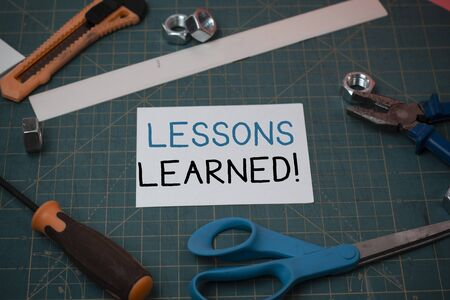 Handwriting text Lessons Learned. Conceptual photo experiences distilled project that should actively taken Carpentry equipments and plain paper scattered everywhere on measuring mat