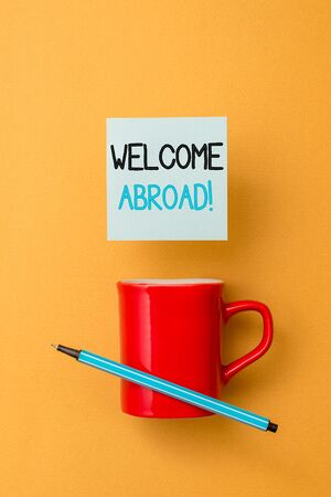 Writing note showing Welcome Abroad. Business concept for something that you say when someone gets on ship Front view coffee cup colored sticky note pen yolk color background