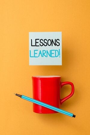 Writing note showing Lessons Learned. Business concept for experiences distilled project that should actively taken Front view coffee cup colored sticky note pen yolk color background