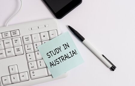 Handwriting text writing Study In Australia. Conceptual photo going into foreign country order complete your studies White pc keyboard with empty note paper above white background