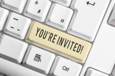 Handwriting text You Re Invited. Conceptual photo make a polite friendly request to someone go somewhere White pc keyboard with empty note paper above white background key copy space Stockfoto