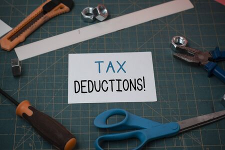 Handwriting text Tax Deductions. Conceptual photo reduction income that is able to be taxed of expenses Carpentry equipments and plain paper scattered everywhere on measuring mat Imagens