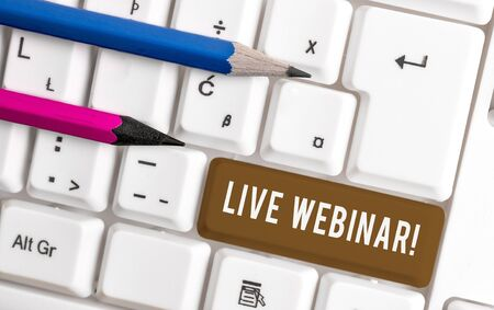 Conceptual hand writing showing Live Webinar. Concept meaning presentation lecture or seminar transmitted over Web White pc keyboard with note paper above the white background Banco de Imagens