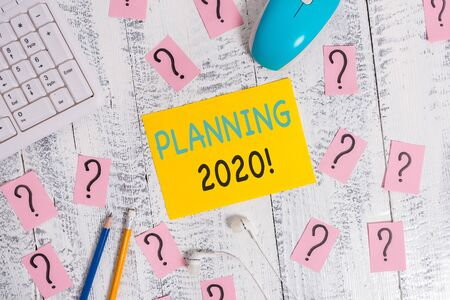 Writing note showing Planning 2020. Business concept for process of making plans for something next year Writing tools and scribbled paper on top of the wooden table Stockfoto